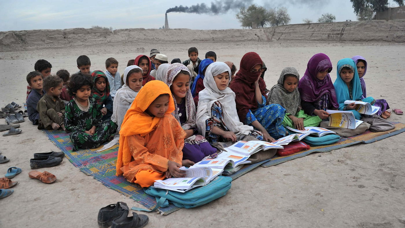 Afghan schoolgirls take lessons outdoors at a refugee camp near Jalalabad.